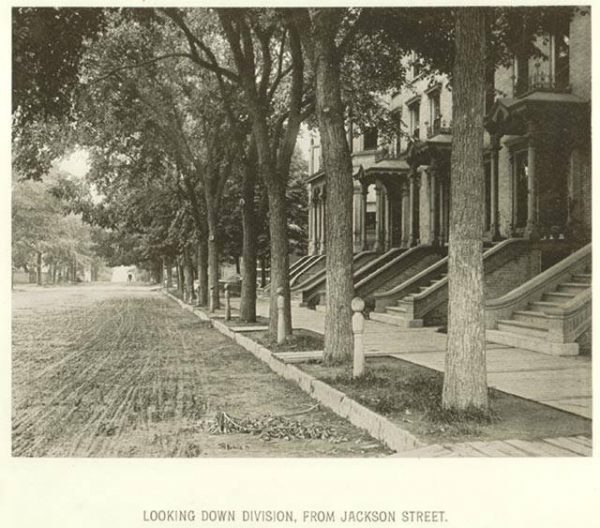 This 1885 view down Juneau Avenue features a tree-lined street and several residences.
