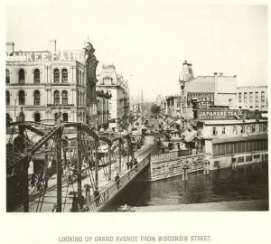 This 1885 view from the east bank of the Milwaukee River features a bustling Grand Avenue.