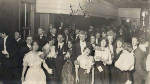 A group of young people, including minors, are photographed inside Vizey's Hall on 8th and Walnut Streets in 1914. The dance hall had two different bars.
