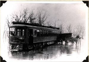 A conductor leans from the window of this interurban car as it sits on a flooded Milwaukee street in this 1906 photograph.