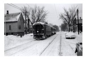 An interurban streetcar traverses a snowy Milwaukee neighborhood in this twentieth century photograph.