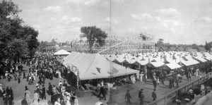 Crowds gather at Pabst Park in the early twentieth century. The park's iconic rollercoaster stands in the background with tents and picnic tables in the foreground.
