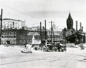 At the right of this photograph, a train leaves the Chicago, Milwaukee, St. Paul, and Pacific Railway depot while its iconic clock tower stands in the background.