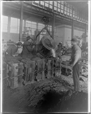 Men working at Manyard Steel pour molten steel into molds during the early twentieth century.