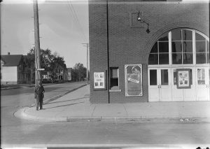 A man stands outside the Layton Park Theatre in 1921. Posters on the outside of the theater advertise for an upcoming show.
