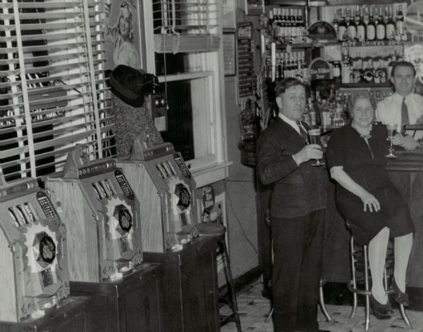 In this photograph from 1942, three slot machines line the wall of the Star Bar and Grill Room in Kenosha County.