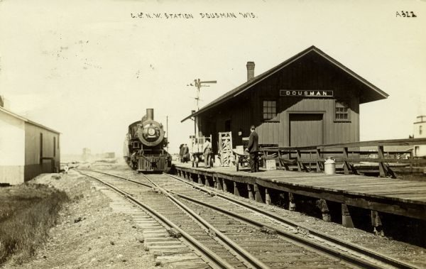 The Chicago and North Western Railway first built a station in Dousman in the 1880s. It is pictured here in 1910 with several individuals standing on the platform.