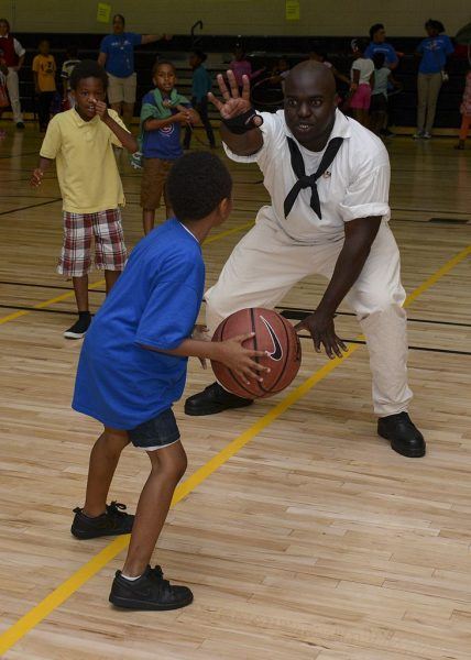 In 2016, Milwaukee was one of several American cities that participated in Navy Week. In this photograph, a serviceman plays basketball with young campers at the Boys and Girls Club of Greater Milwaukee.