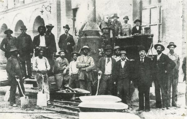 A group of African American construction workers, along with some Caucasian men, pose for a photograph as they work on Milwaukee's City Hall in 1896.