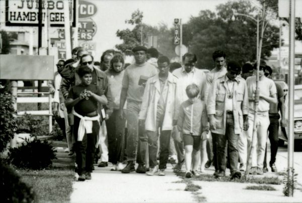 A group of protestors, led by Father James Groppi, participate in a welfare march from Milwaukee to Madison in 1969.