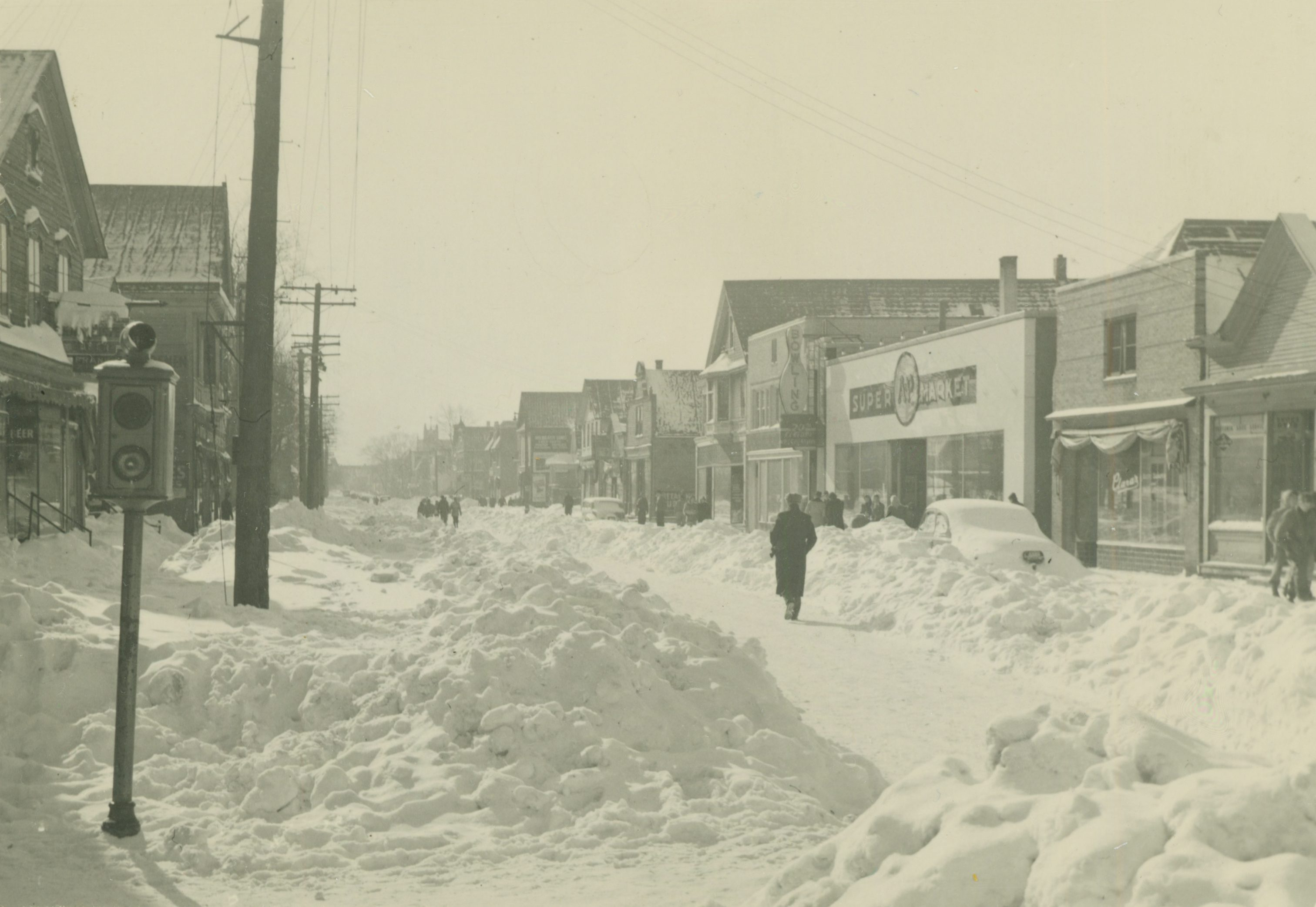 In 1947, a January blizzard brought sixteen inches of snowfall to Milwaukee and crippled the city. Pictured here the day after the storm, Teutonia Avenue is only partially plowed and snow drifts are piled high along the sidewalks.