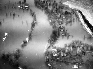 This undated aerial photograph showcases extensive flooding along the Milwaukee River. A number of homes are completely surrounded by water.