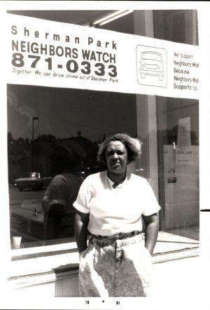 Sherman Park resident Shirley Warren stands outside a local building in 1991. The banner above her promotes a neighborhood watch and community safety.