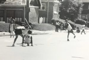 Pictured here in the late 1980s, a group of children play baseball in the street in the Sherman Park neighborhood.