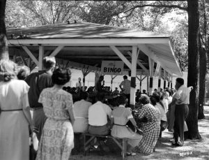 A group of people gather under an outdoor structure for bingo in 1950. Playing bingo for money, even for charitable purposes, was technically not legal until 1973.