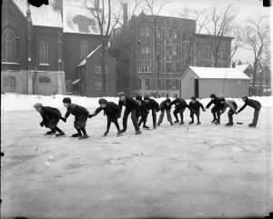 A group of young boys form a chain while ice skating together in this photograph from the twentieth century.