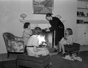 A woman stands in front of a fireplace with three young girls at the YWCA in 1936.