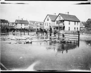 In this 1912 photograph, men work with poles to relieve river flooding along the Fourth Avenue bridge.
