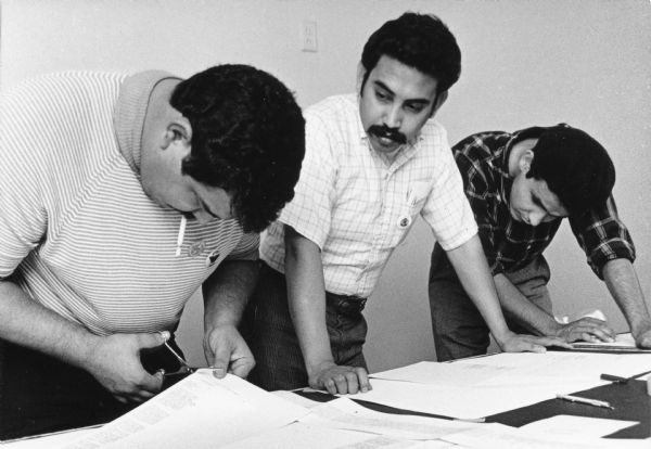 "Roberto Hernandez (left), along with Esequiel Guzman (center) and another man work to set the layout of an issue of the ""La Guardia"" newspaper."