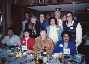 Congresswoman Patricia Schroeder of Colorado (standing, second from left) and Ellen Bravo (standing, third from left), along with other women, are gathered together for a 9to5 Milwaukee chapter event.