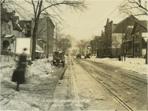 This 1923 photograph provides a view down Wells Street just west of 27th Street. There is a mixture of residential and commercial buildings in the neighborhood.