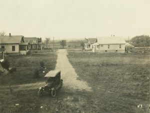 Taken in West Allis in the early 20th century, a small cluster of houses on McMyron Street sit in a primarily rural landscape. Note the automobile in the foreground, which gave suburban residents mobility around the metropolitan area.