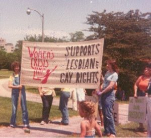 Members from the Women's Crisis Line, a program within the Women's Coalition of Milwaukee, provide support at a gay rights parade in 1979.