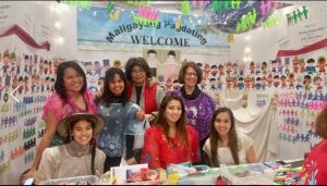 Members of Milwaukee's Filipino community welcome visitors to a crafting table at a cultural event.