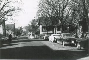This residential section of W. Lloyd Street from 5th Street is lined with homes, trees, and cars in 1958.