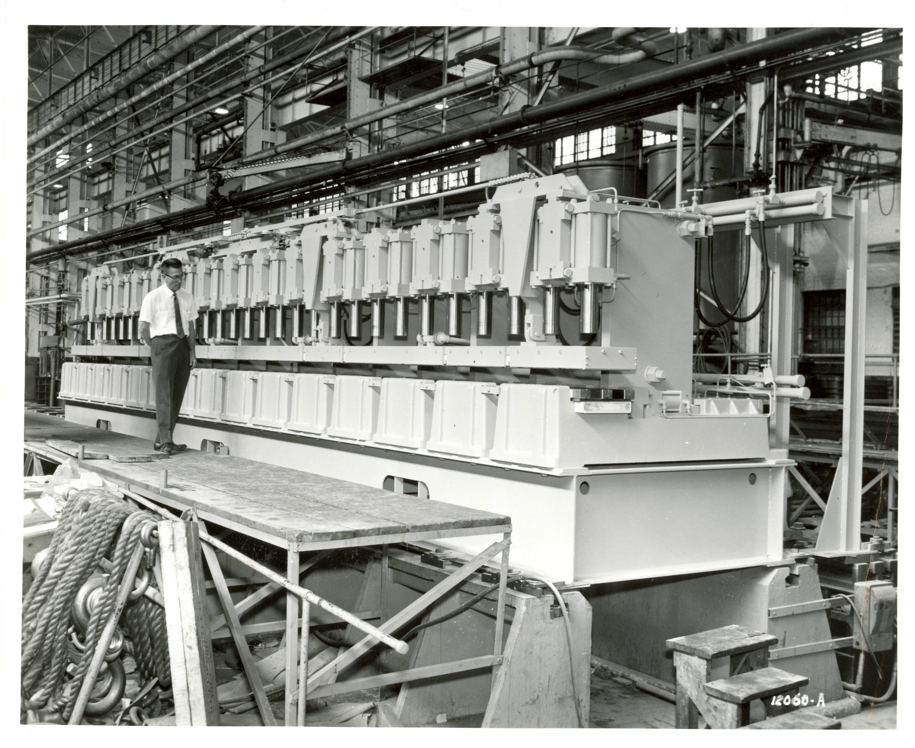 A man stands on scaffolding next to a large molding press at the Nordberg Manufacturing Company.