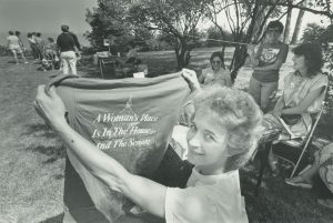 """Cheryl Keenan, Milwaukee's representative in the National Organization for Women holds a shirt that reads """"A woman's place is in the House...and the Senate"""" at the city's first women's festival in 1984."""