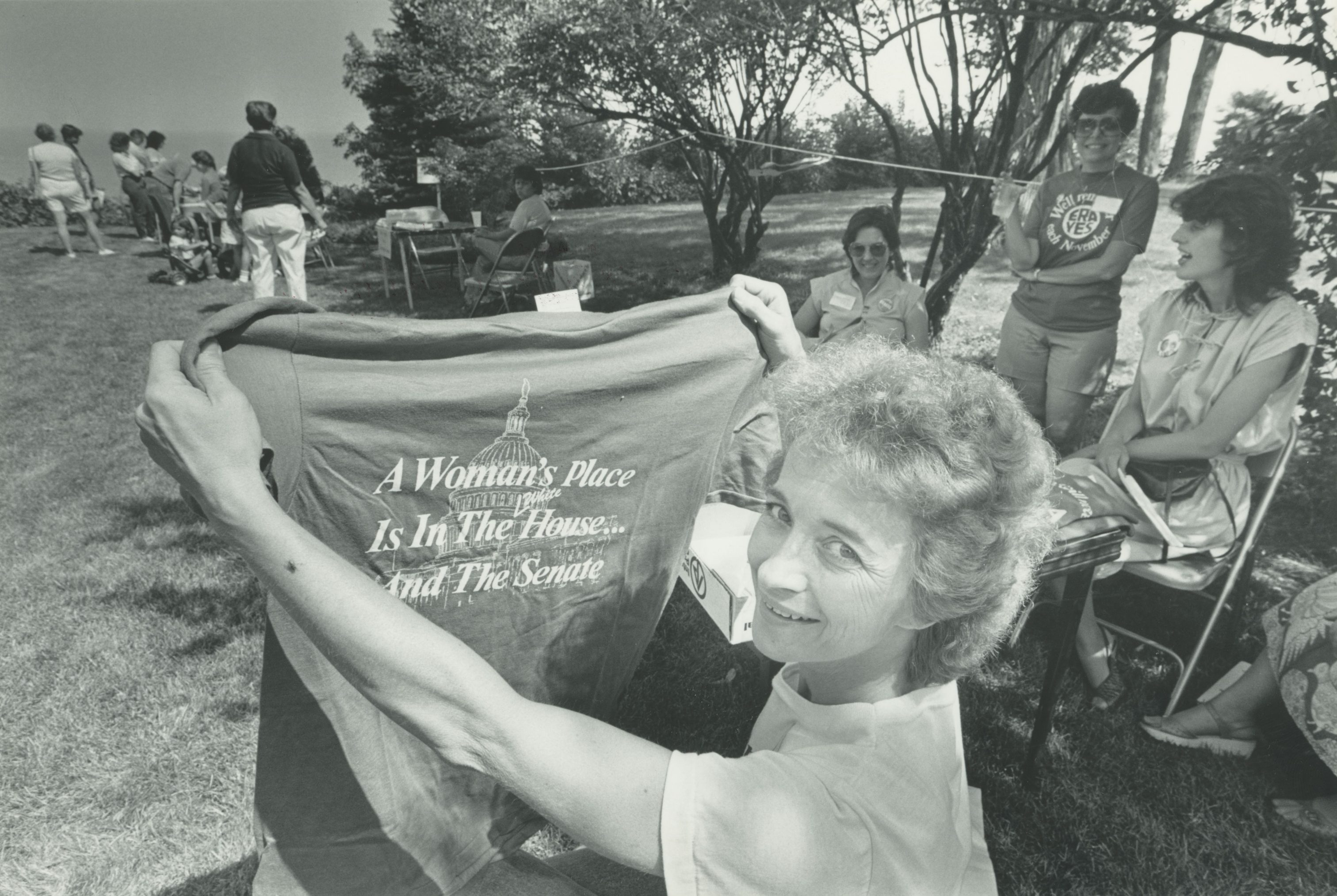 "Cheryl Keenan, Milwaukee's representative in the National Organization for Women holds a shirt that reads ""A woman's place is in the House...and the Senate"" at the city's first women's festival in 1984."