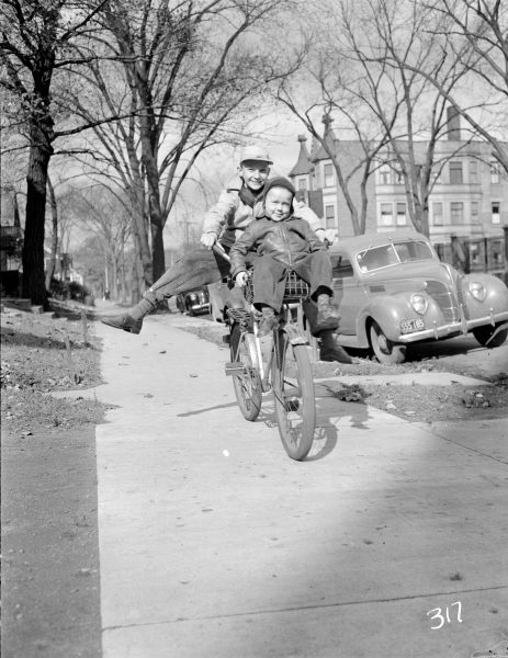 Two children share a bike as they ride down a Milwaukee sidewalk in October 1943.
