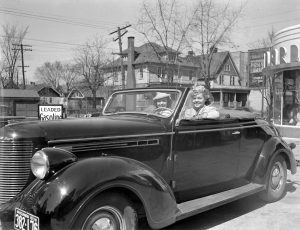 Two women sit in their car at a service station and smile for the camera in 1939.