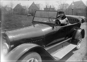 A woman sits in a touring automobile in 1917.