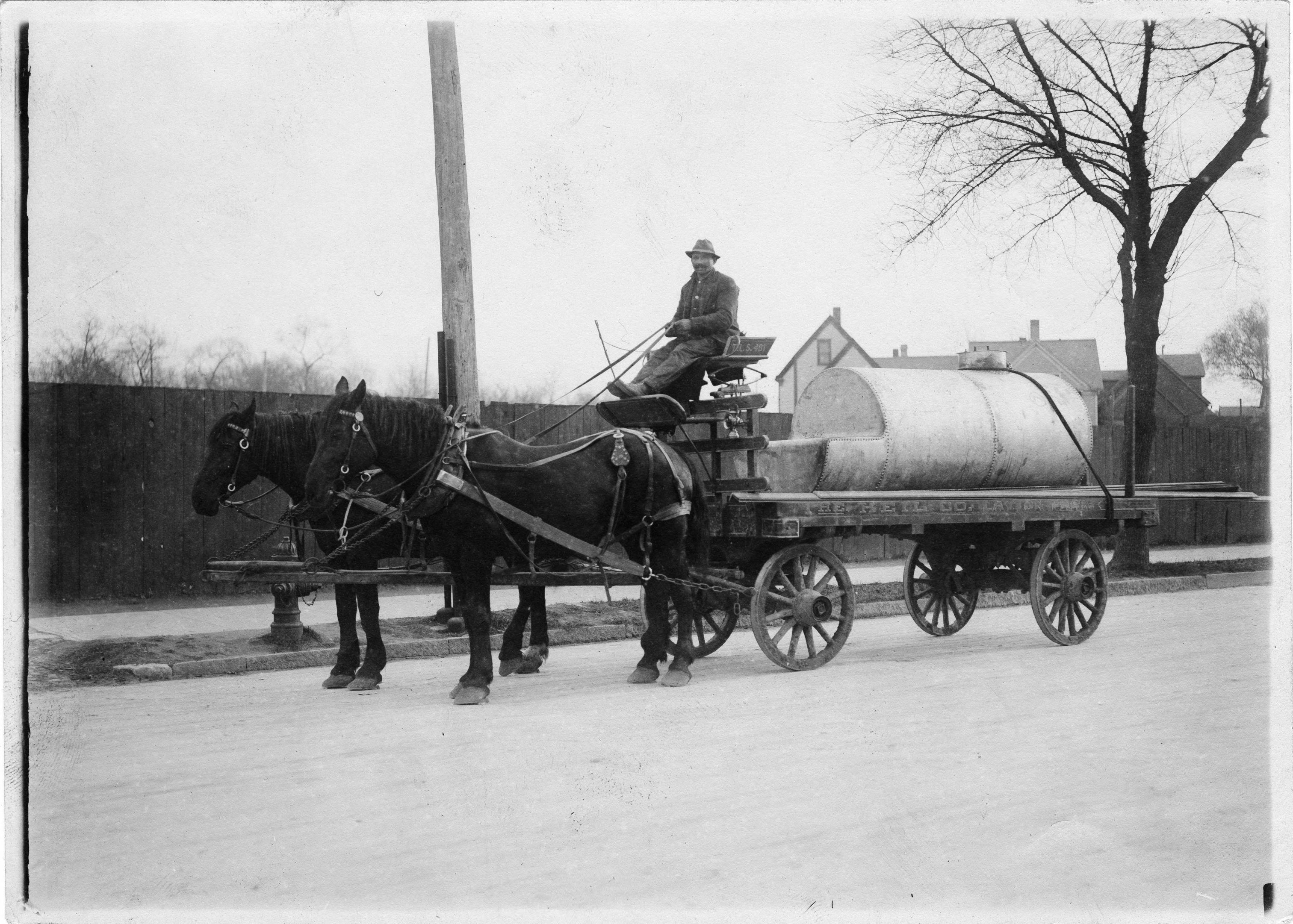 A man sits atop a horse-drawn wagon carrying a metal tank. The wagon is labelled as belonging to the Heil Company, located in the Layton Park neighborhood.