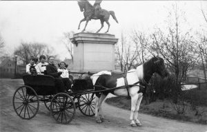 Four people sit in a horse-drawn wagon in front of the Kosciuszko Monument in Kosciuszko Park on Milwaukee's South Side.
