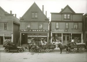 A horse-drawn wagon and two early cars sit out front of the William J. Branta Furnishings Company on Lincoln Avenue in 1907. Next to the furniture store, Branta owned a second storefront that sold appliances.