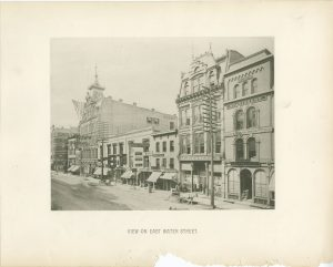 Taken in the 1880s, this block of Water Street between Wisconsin and Mason Streets features a wide variety of businesses, including a furniture store, saloon, tailor, printer and bindery, and bookstore.