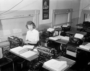 A woman sits in an office full of typewriter workstations as she works for the Schellin Letter Service in 1945.