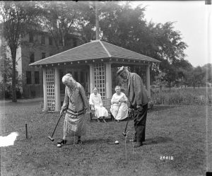 An older couple plays bocce ball while two other women watch from a bench nearby.