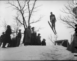 A man ski jumps from a wooden ramp while a crowd watches.