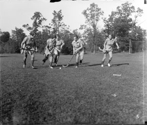 Five young women from Milwaukee-Downer College play field hockey in this photograph from 1935.