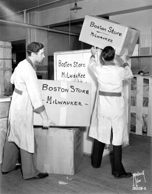 Two men employed by Boston Store move boxes in 1938.