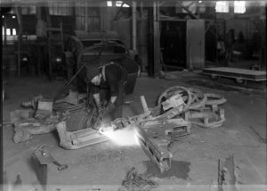 A man works to weld pieces of metal together at the Maynard Electric Steel Casting Company in the early twentieth century.