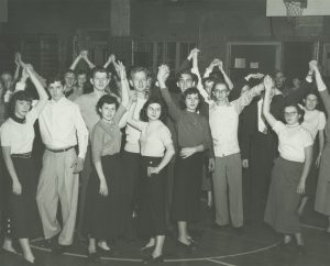 """High school students a Halloween dance in 1953. A caption on the back of the photo calls them """"happy and out of mischief."""""""