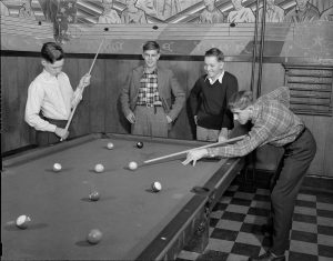 Four boys shoot pool together.