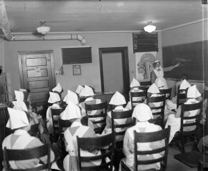 A classroom full of nursing students listen to a lecture in 1925.