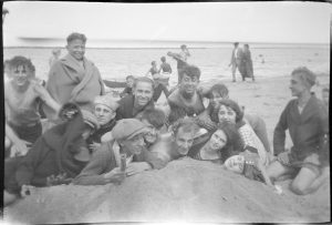 A group of young men and women enjoy a day at the beach during the first half of the twentieth century.
