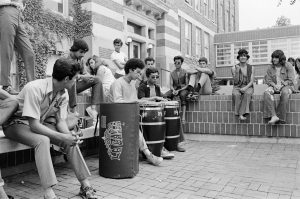 A group of students are gathered in a drum circle outside Mitchell Hall during the 1970 protests that led to the creation of the Spanish Speaking Outreach Institute at UWM.